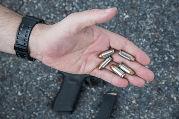 Bullets in man's palm with gun and clip