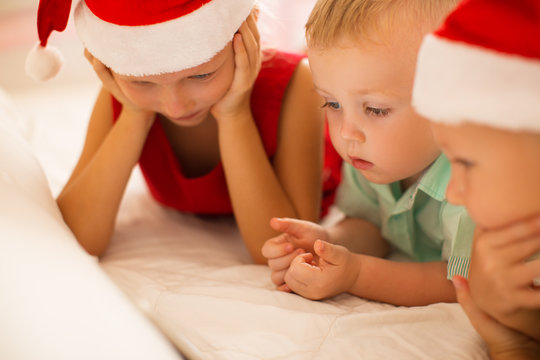 Curious kids watching Christmas movie on device