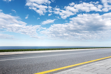 empty asphalt road with blue sea in blue sky
