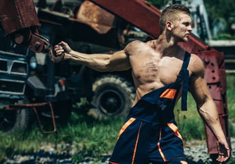 Bodybuilder with muscle chest, hands, biceps, triceps pull iron crane