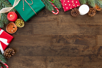 Christmas holiday gift boxes with decorating items on dark brown wooden table background