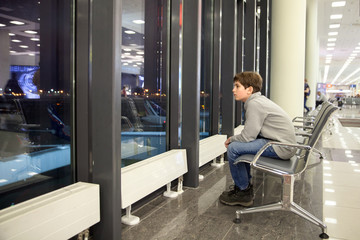 A boy is siting in hall of airport and waiting of boarding in night time