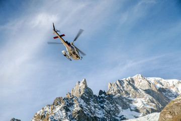 A rescue helicopter over mountains in Alps, France