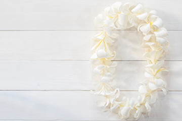 White Plumeria Flower lei garland flat lay on natural white pine wood background for Hawaii Lei day concept