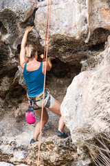 Young woman climber climbing on the rock outdoors