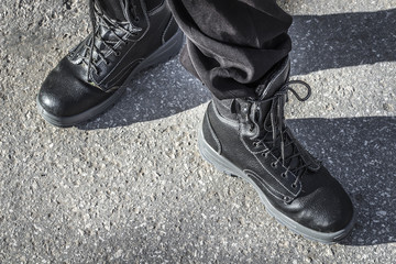 Black rough boots on the feet of a man on the background of asphalt.