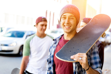Teenager boy walking at the street with his skateboard