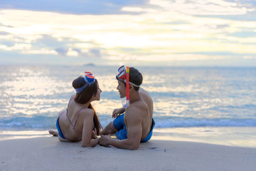 Happy young couple with snorkelling gear enjoy together on a sea beach.