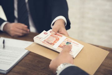 Businessman giving Russian Ruble money to his partner
