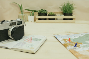 camera, passport,  world map with pins 2 pieces point on map placed on wooden table has plants in vase are background. this image for business, travel, photography, equipment, map concept