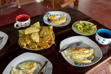 Breakfast table with fried eggs, scrambled eggs, pineapple, avocado, coffee