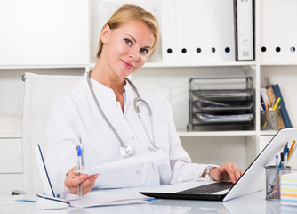 portrait of young  doctor writing and working with laptop in office