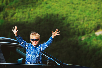 happy little boy travel by car in nature