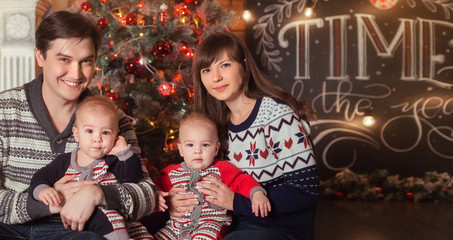 Merry Christmas and Happy New Year 2018 Holidays concept. Cheerful mom, dad and cute twins baby boys smiling. Parents and two little children having fun and playing together near Christmas tree