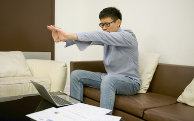 Asian businessman stretching in front of laptop with documents