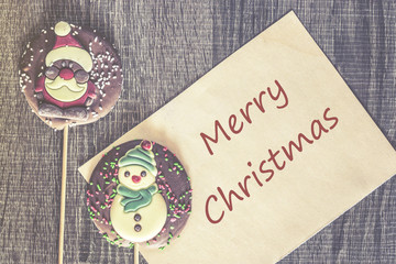Merry Christmas wish and Christmas candy on a wooden background. Table top view