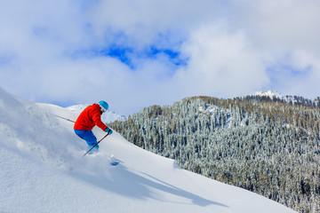 Man skiing on fresh powder snow in Italian Alps.