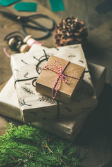 Preparing for Christmas or New Year holiday. Gift boxes, rope, fur branches, scissors over rustic wooden table background, selective focus