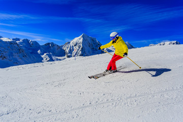 Woman skiing on snow on a sunny day in the mountains. Ski in winter seasonon, the tops of snowy mountains in sunny day. South Tirol, Solda in Italy.