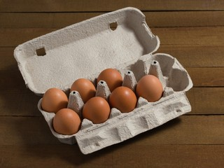 Cardboard box with chicken eggs on a wooden table.