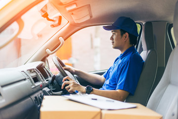 Young handsome delivery man driving his van with packages on the front seat Fototapete