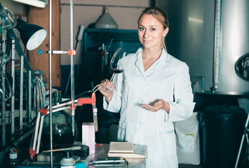 cheerful female specialist in winery laboratory