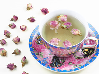 Cup of rose bud tea on a white wooden board, framed by dried rose buds