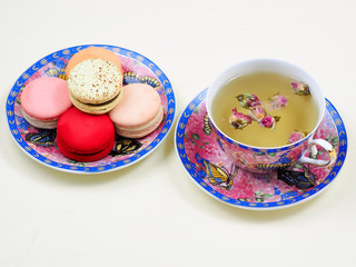 Cup of rose bud tea in a pretty floral cup and saucer served with a matching plate of traditional colorful French macarons over a white background