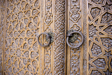 An old wood door with metal handle. Details of Muslim architecture.