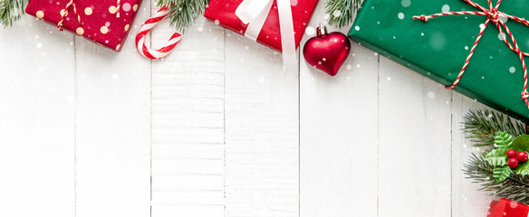 Christmas gift boxes with decorating ornaments on white wood background border design