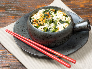 Bowl of healthy fresh vegetables with Asian noodles served with chopsticks in a bowl over a rustic wooden table