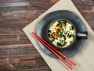 Bowl of healthy fresh vegetables with Asian noodles served with chopsticks in a bowl in a top down view over a rustic wooden table, with copy space