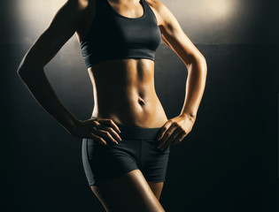 Fit body of beautiful, healthy and sporty woman. Slim woman posing in sportswear.
