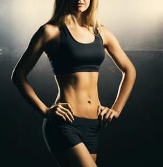 Fit body of beautiful, healthy and sporty woman. Slim woman posing in sportswear.