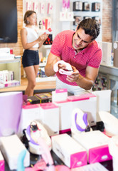 female and male purchasers touching in the modern sex shop different sexy toys