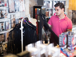 Buyer  man choosing black sexual shirt in the sex shop