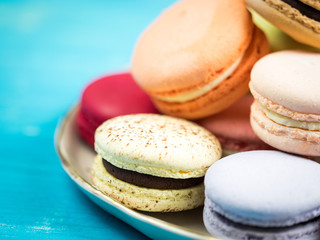 Traditional brightly colored French macaroons on a hand-made plate, set on a blue wooden board, close-up view