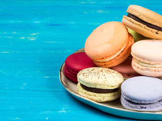 Traditional brightly colored French macaroons on a hand-made plate, set on a blue wooden board, close-up view with copy space