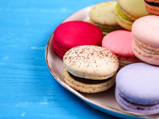 Traditional brightly colored French macaroons on a hand-made plate, set on a blue wooden board, close-up view, selective focus