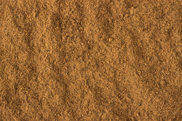 ground nutmeg powder spice as a background, natural seasoning texture