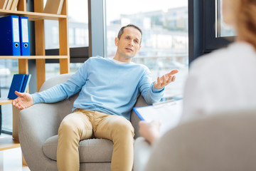 Psychological therapy. Nice pleasant handsome man sitting in the armchair and talking to his doctor while undergoing psychological therapy