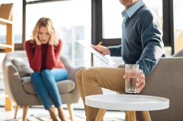 Psychologists office. Selective focus of a glass of water being put on the table by a nice handsome male psychologist while working with a patient