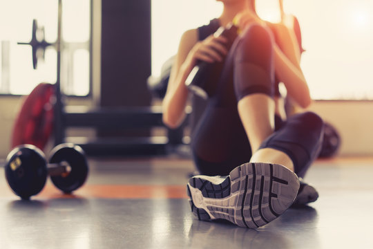 Woman exercise workout in gym fitness breaking relax holding protein shake bottle after training sport with dumbbell and healthy lifestyle bodybuilding.