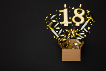 Number 18 gold celebration candle and gift box background