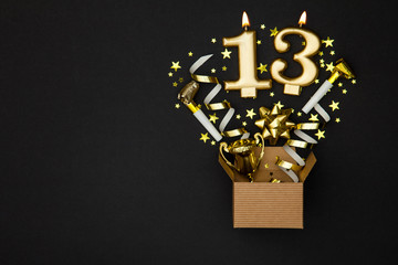 Number 13 gold celebration candle and gift box background