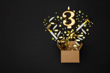 Number 3 gold celebration candle and gift box background