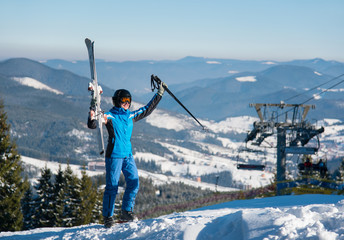 Full length shot of a happy woman posing with her skis on top of the mountains celebrating success holding her equipment up in the air, smiling joyfully copyspace. Bukovel
