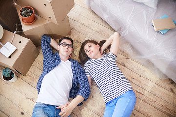 High angle view of loving young couple lying on floor of living room and dreaming about their cohabitation in new apartment, pile of moving boxes standing next to them