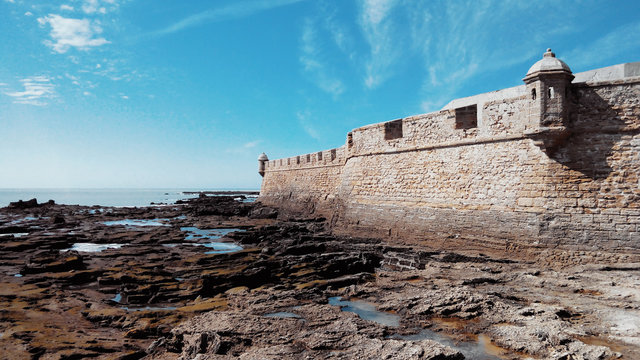 Fortress of San Sebastian, low tide and stones covered with algae on a sunny day in Cadiz, Andalusia, Spain.