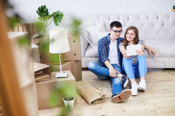 Full length portrait of lovely young couple wearing jeans and T-shirts taking selfie with help of digital tablet while sitting on wooden floor of new apartment, piles of moving boxes on background